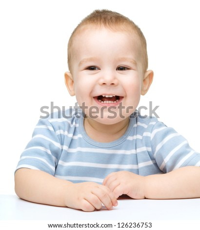 Portrait of a cute little boy sitting at table, isolated over white - stock photo