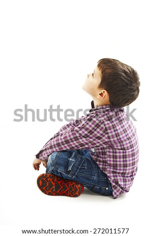 Portrait of a cute little boy sitting on the floor, looking up. Isolated on white background   - stock photo