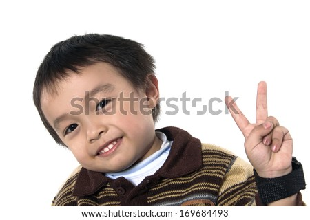portrait of a cute little boy smiling -two fingers of kid's hand isolated - stock photo