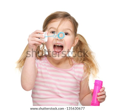 Portrait of a cute little girl blowing soap bubbles - stock photo