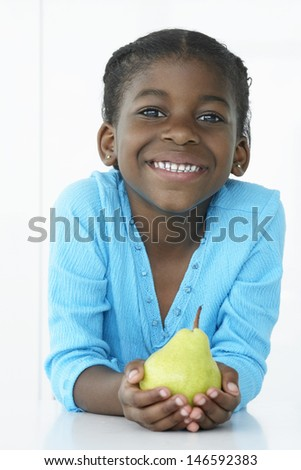 Portrait of a cute little girl holding pear against white background - stock photo