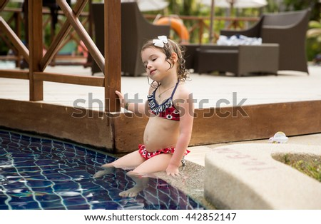 Portrait of a cute little girl in swimming pool. A beautiful kid in swimsuit sitting at the blue water of swimming pool. Looking at the water surface and enjoying summer vacation in tropic resort. - stock photo
