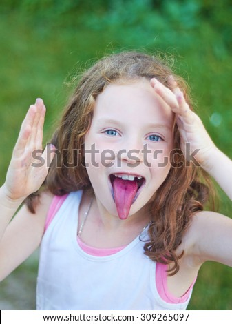 Portrait of a cute little girl that shows tongue after eating berries - stock photo