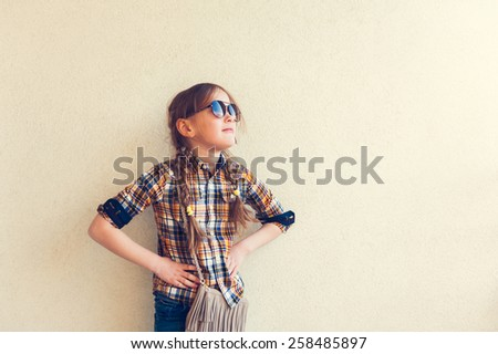 Portrait of a cute little girl wearing yellow and blue plaid shirt and sunglasses - stock photo