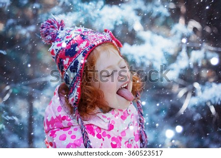 Portrait of a cute little girl who catches snowflakes mouth in winter day. - stock photo