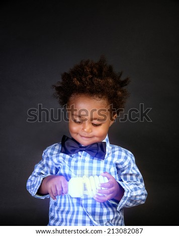Portrait of a cute little schoolboy holding in hands bright lamp, smart boy learning science  - stock photo