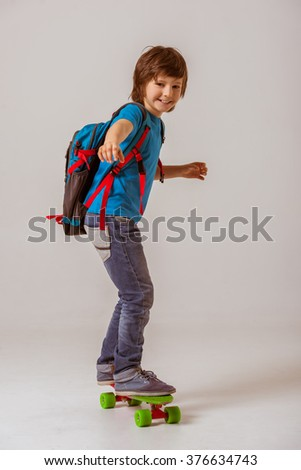 Portrait of a cute little schoolboy in a blue t-shirt with a backpack looking in camera and smiling while skateboarding on a gray background - stock photo