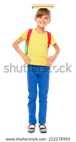 Portrait of a cute little schoolgirl with backpack holding book on her head, isolated over white - stock photo