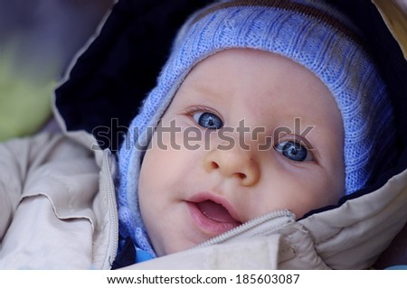 Portrait of a cute 6 month old baby with huge blue eyes in buggy outdoors on walking - stock photo