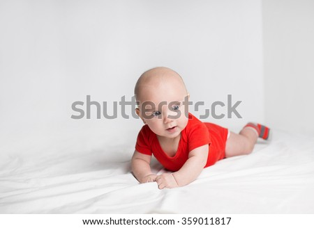 Portrait of a cute 5 months old baby boy in a red onesie lying down on a white blanket, looking aside - stock photo