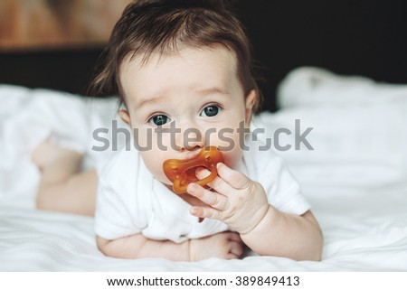 Portrait of a cute 4 months old baby with nipple lying down on a bed - stock photo