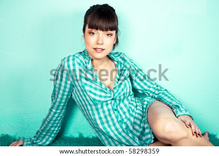 Portrait of a cute pretty woman styled like a pin-up looking at camera with a turquoise background - stock photo