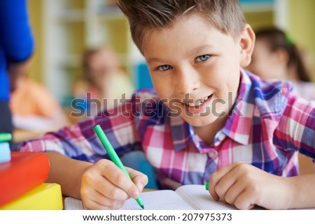 Portrait of a cute schoolboy looking at camera while drawing at lesson - stock photo