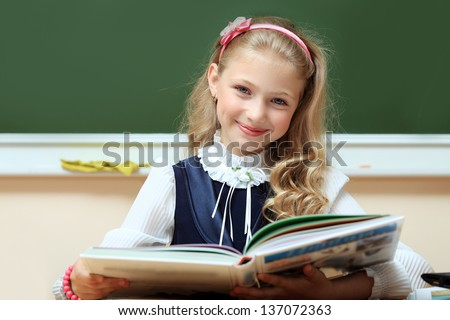 Portrait of a cute schoolgirl in a classroom. - stock photo