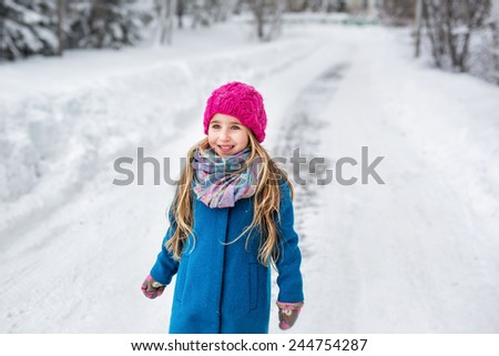 Portrait of a cute six year old girl with long blond hair, dressed in a blue coat and a pink hat in the winter forest - stock photo