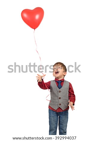 Portrait of a cute smiling little boy with red heart shaped balloon isolated on white background - stock photo