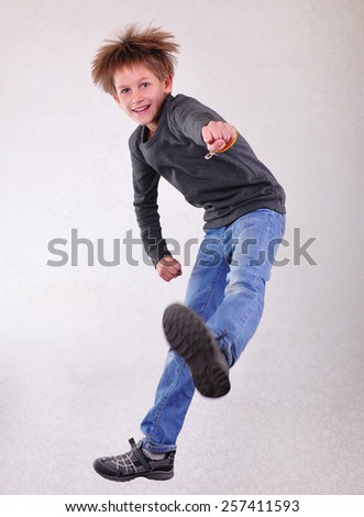 Portrait of a cute  sportive, cheerful happy boy with his hands up jumping and dancing. Childhood, freedom, happiness concept. - stock photo