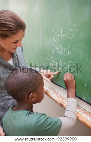 Portrait of a cute teacher and a pupil making an addition on a blackboard - stock photo