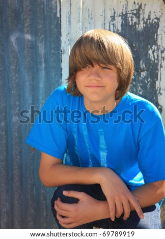 portrait of a cute teen boy with fashionable shaggy hair in front of a corrugated metal wall. - stock photo