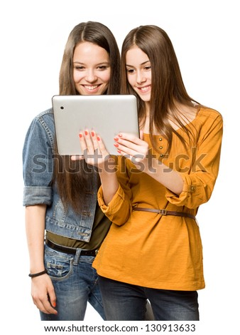 Portrait of a cute teen girls sharing a tablet computer. - stock photo