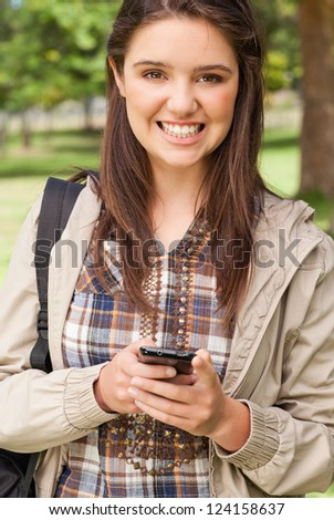 Portrait of a cute teenager with a smartphone in a park - stock photo