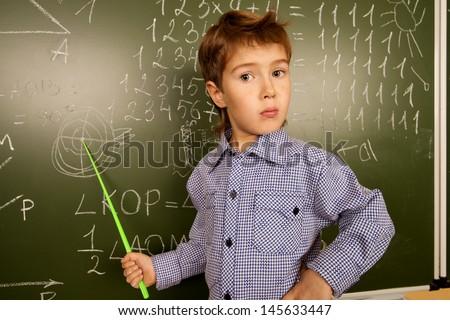 Portrait of a cute thoughtful schoolboy near the blackboard in a classroom. - stock photo