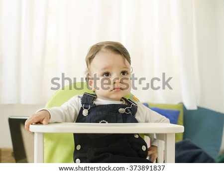 Portrait of a cute toddler. Beautiful baby boy sitting in a high chair waiting, looking away. - stock photo