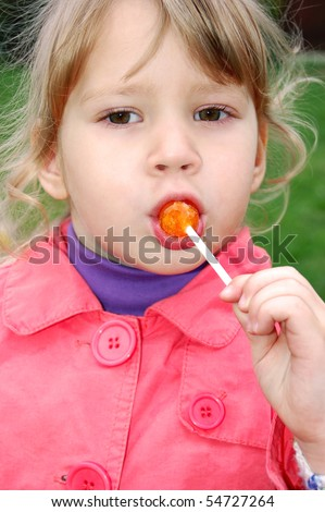 Portrait of a cute toddler eating a lollipop - stock photo