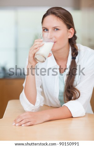 Portrait of a cute woman drinking milk in her kitchen - stock photo
