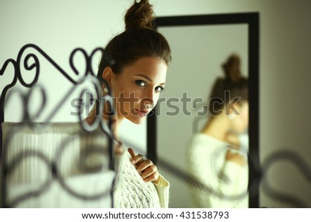 Portrait of a cute woman in sweater at home - stock photo