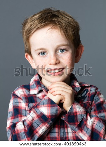 portrait of a cute 5-year old preschooler with blue eyes and freckles smiling for sweet childhood, grey background studio - stock photo