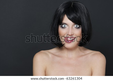 Portrait of a cute young brunette licking her lips and making face - stock photo