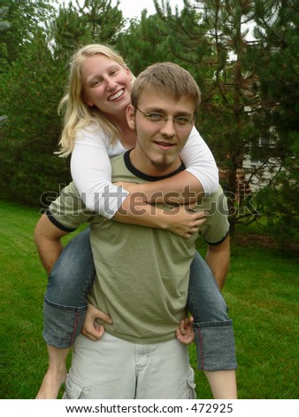 Portrait of a cute young couple, girl on piggy-back - stock photo