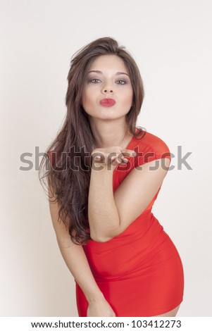 Portrait of a cute young female blowing a kiss at you against white background - stock photo