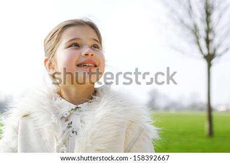 Portrait of a cute young girl child smiling and being joyful while in a green park during a sunny winter day, looking up to the sky and wearing a warm coat, outdoors. - stock photo