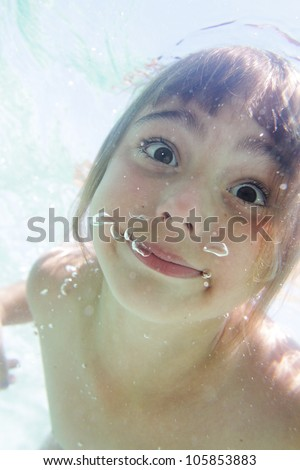 Portrait of a cute young girl submerging herself into a blue water - stock photo