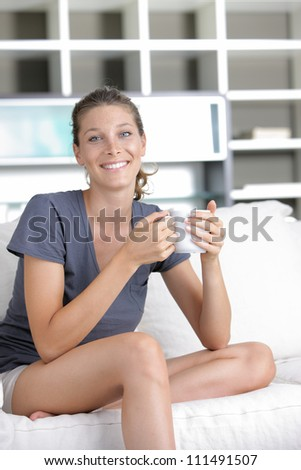 Portrait of a cute young lady sitting on sofa with a cup of coffee - stock photo