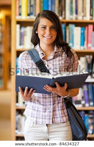 Portrait of a cute young student holding a book in the library - stock photo
