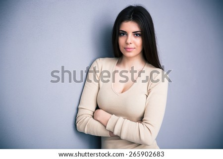 Portrait of a cute young woman with arms folded standing over gray background. Looking at camera.  - stock photo