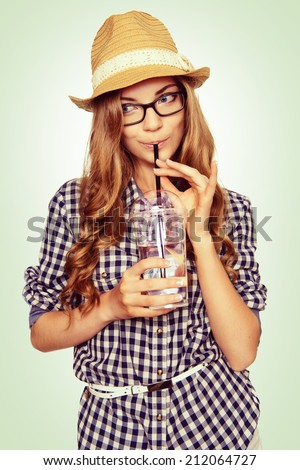 portrait of a cute young woman with casual garb drinking water through a straw. studio shot.  - stock photo