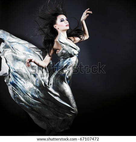 Portrait of a dancing sexy young woman with flying hair and silk dress - stock photo