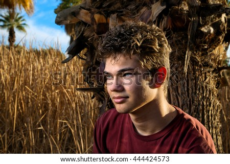 Portrait of a dark haired teenage boy in a maroon shirt.  There is dramatic lighting on his deep, blue eyes. - stock photo