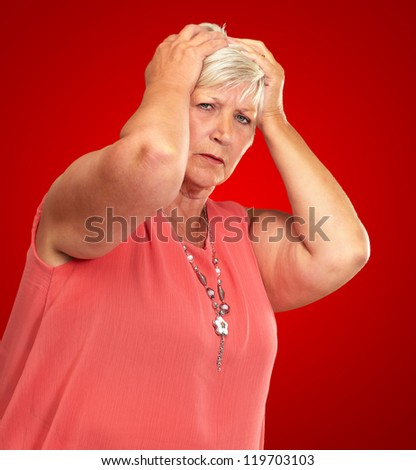 Portrait Of A Depressed Senior Woman On A Red Background - stock photo