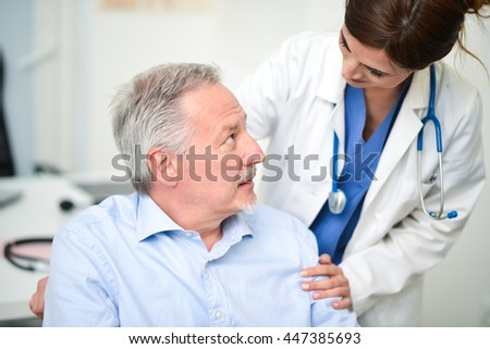 Portrait of a disabled patient talking to a doctor - stock photo