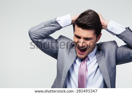 Portrait of a disappointed businessman over gray background - stock photo