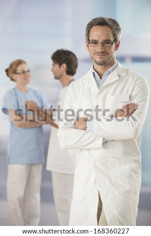 portrait of a doctor arms crossed in hospital - stock photo