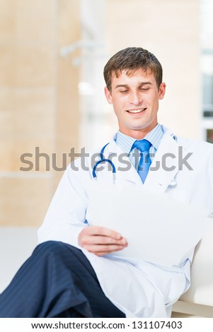 Portrait of a doctor holding papers in hand, office space - stock photo