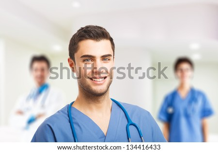 Portrait of a doctor in front of his medical team - stock photo