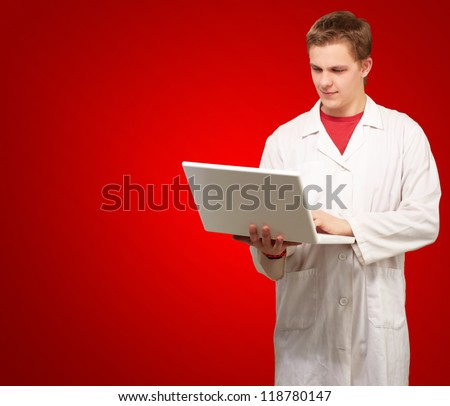 Portrait of a doctor surfing on laptop on red background - stock photo
