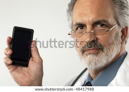 Portrait of a doctor wearing glasses and a white lab coat.  He is holding up a cell phone and looking at the camera. Horizontal shot. - stock photo